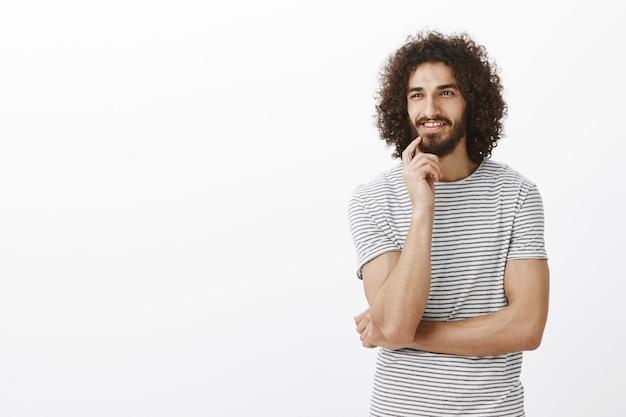 Geïntrigeerde gelukkige bebaarde man met afrokapsel en baard, opzij kijkend, vinger op de lip vasthoudend en nieuwsgierig glimlachend, denkend aan iets lekkers of interessants