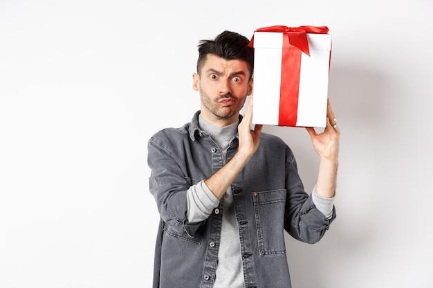 Geïntrigeerde jongeman die verward naar de camera kijkt, probeert te raden wat er in de geschenkdoos van de minnaar zit, het cadeau schudt en verbaasd staart, staande op wit. valentijnsdag concept.