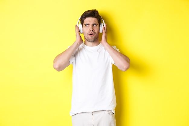 Geïntrigeerde man genieten van deuntjes in koptelefoon, aandachtig luisteren naar muziek in oortelefoons, staande op gele achtergrond.