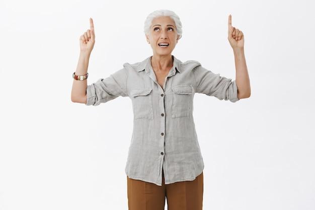 Geïntrigeerde mooie oude dame die vingers omhoog wijst en naar advertentie kijkt