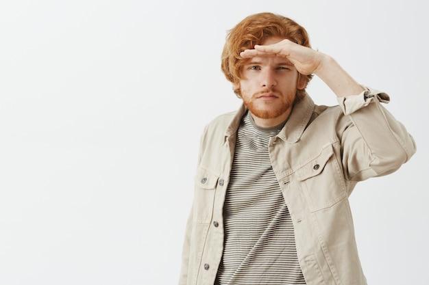 Geïntrigeerde roodharige man met baard die tegen de witte muur poseert