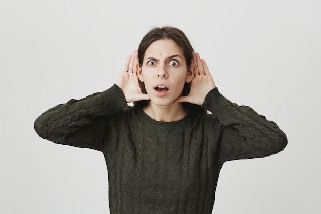 Geïntrigeerde schattige jonge vrouw houdt haar handen in de buurt van oren en luistert af, zoals geruchten
