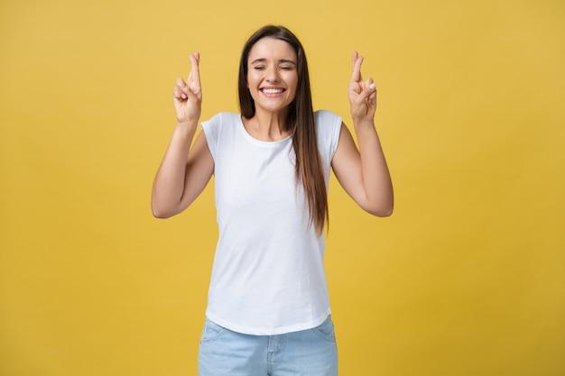 Geïntrigeerde vrouw in t-shirt die met gekruiste vingers bidt en wegkijkt over gele achtergrond