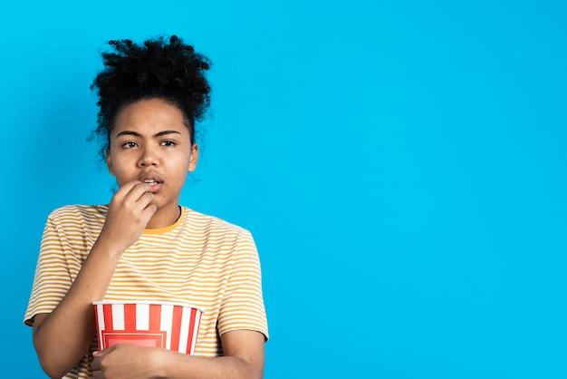 Geïntrigeerde vrouw poseren tijdens het eten van popcorn