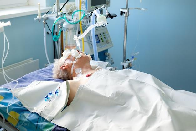 Geïntubeerde volwassen blanke man onder avl liggend in coma op de afdeling intensive care. kritieke toestand.