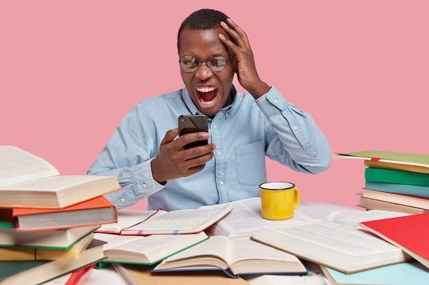 Geïrriteerd boos donkere huid jonge man kijkt met ontevredenheid knorrige gezichtsuitdrukking naar mobiele telefoon, gekleed in formeel shirt, houdt de hand op het hoofd