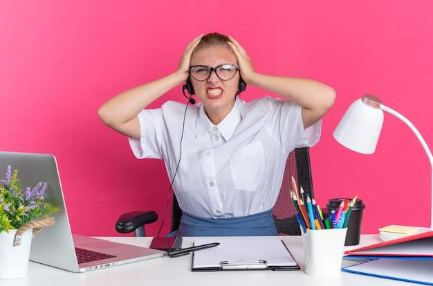 Geïrriteerd jong blond callcentermeisje met hoofdtelefoon en bril zittend aan een bureau met uitrustingsstukken die de handen op het hoofd houden en kijken naar de camera met tanden die op roze muur worden geïsoleerd