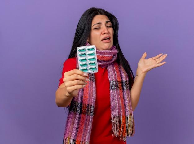 Geïrriteerd jong kaukasisch ziek meisje dat sjaal draagt die uit pak capsules uitrekt die lege hand met gesloten ogen toont die op purpere muur met exemplaarruimte wordt geïsoleerd