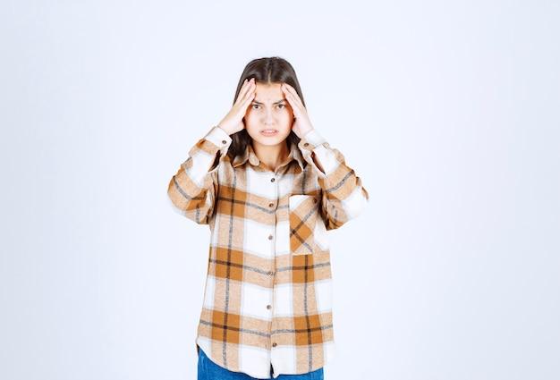 Geïrriteerd jong meisjesmodel dat haar hoofd houdt en aan pijn lijdt.