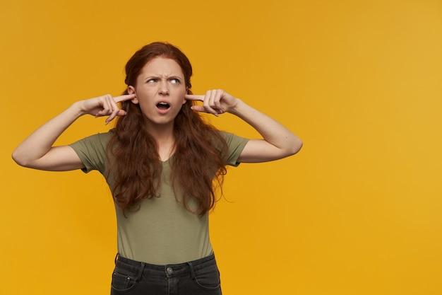 Geïrriteerd uitziend meisje, fronsende roodharige vrouw met lang haar. groen t-shirt dragen. emotie concept. sluit haar oren met de vingers. kijken naar rechts op kopie ruimte, geïsoleerd over oranje muur