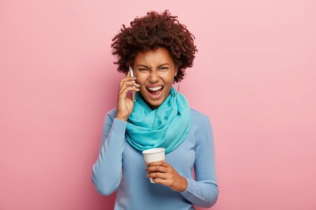 Geïrriteerde afro-vrouw heeft ruzie via smartphone, schreeuwt luid van frustratie, houdt afhaalmaaltijden koffiekopje vast, draagt blauwe trui met sjaal
