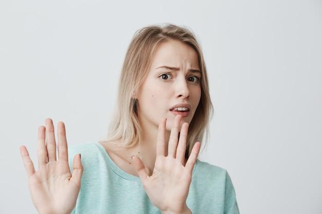 Geïrriteerde, bang, blonde, jonge vrouw met recht blond haar in blauwe trui die tegen de muur poseert, de handen in een stopgebaar houdt, zichzelf probeert te verdedigen en zegt: stop daarmee. lichaamstaal.