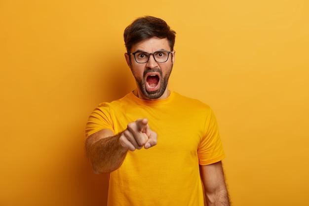 Geïrriteerde, bebaarde jongeman schreeuwt boos, beschuldigt iemand