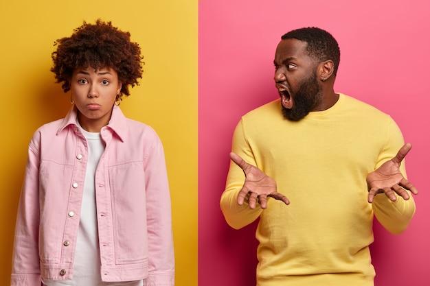 Geïrriteerde bebaarde man schreeuwt boos naar vriendin, beschuldigt van iets verkeerds, steekt handpalmen op