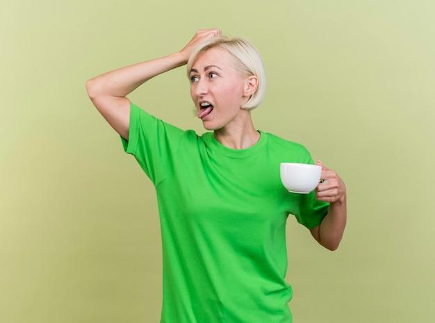 Geïrriteerde blonde slavische vrouw van middelbare leeftijd met kopje thee aanraken van hoofd kijken naar kant tonen tong geïsoleerd op olijfgroene muur