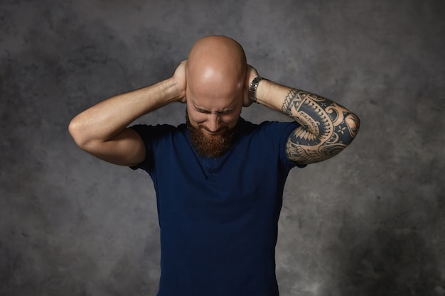 Geïrriteerde boze kale man met tatoeage sluitende ogen en bedekte oren met handen, kan niet tegen het geschreeuw van zijn luide woedende vrouw terwijl ze ruzie heeft. lichaamstaal en menselijke emoties