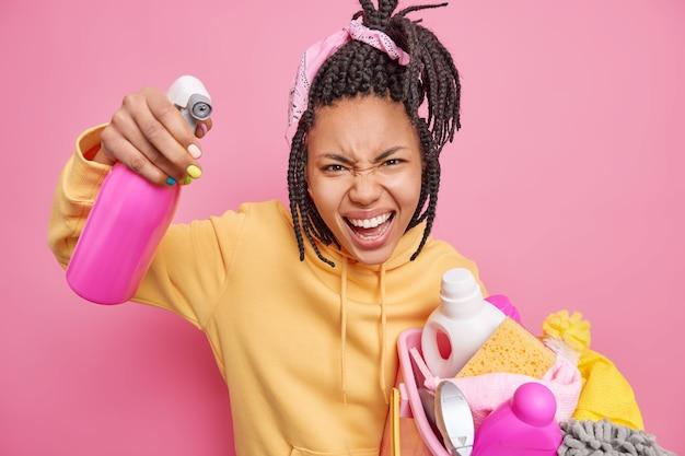Geïrriteerde dienstmeid roept boos uit, drukt negatieve emoties uit houdt een wasbak vol was- en wasmiddelfles vast