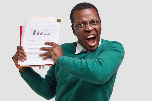 Geïrriteerde donkere man schreeuwt van woede, houdt papieren documenten vast, roept luid uit, voelt zich depressief, vermoeidheid van het werk
