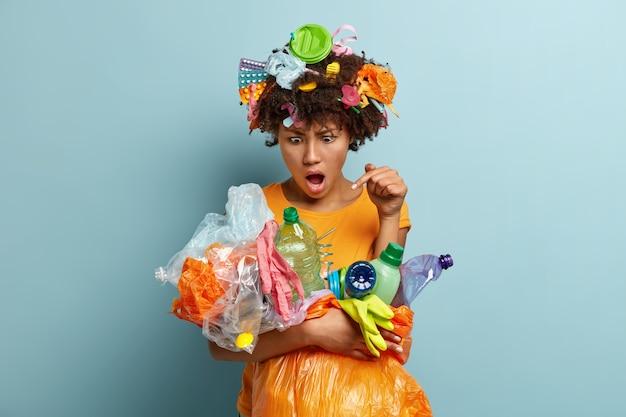 Geïrriteerde emotionele vrouwelijke vrijwilliger met een donkere huid verzamelt plastic flessen en polytheen voorwerpen, vecht tegen natuurrampen of vervuilingsproblemen, verzamelt afval, geïsoleerd tegen blauwe muur