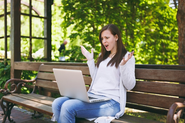 Geïrriteerde en ontevreden zakenvrouw in lichte vrijetijdskleding. vrouw zit op bankje werken op moderne laptop pc-computer in stadspark in de buitenlucht op de natuur. mobiel kantoor. freelance bedrijfsconcept