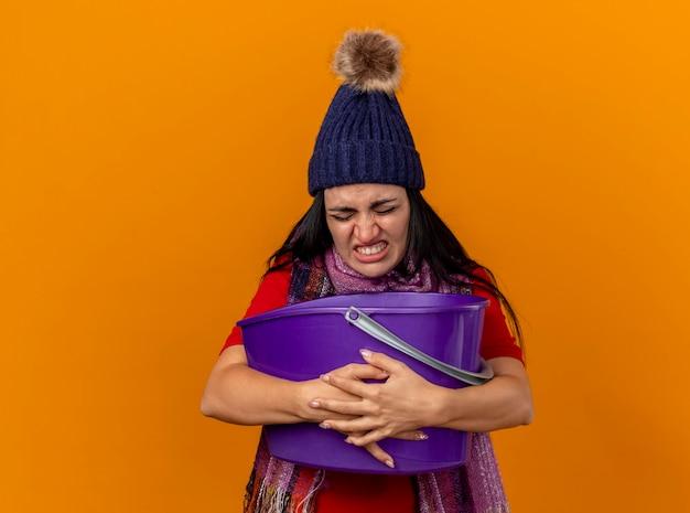 Geïrriteerde en pijnlijke jonge zieke vrouw die de wintermuts en sjaal draagt die plastic emmer houdt met misselijkheid met gesloten ogen geïsoleerd op een oranje muur