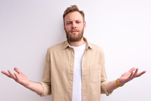 Geïrriteerde geërgerde man met baard heeft problemen, gebaren met handen, crisis en negativiteit, man verkeerd begrijpen schouderophalend naar camera