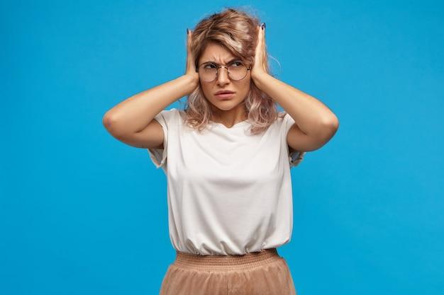 Geïrriteerde gestreste jonge vrouw met ronde bril die de oren bedekt, gestoord met luid slijm