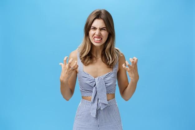 Geïrriteerde humeurige vrouw met zenuwinzinking zich geïrriteerd en onder druk gezet handen in vuisten knijpen van woede rimpelige neus in haat hatelijk staan over blauwe muur