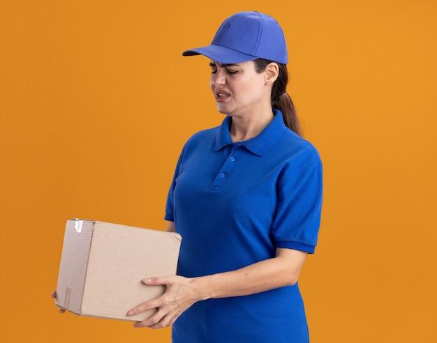 Geïrriteerde jonge bezorger in uniform en pet die in profielweergave staat en kijkt naar cardbox geïsoleerd op oranje muur met kopieerruimte
