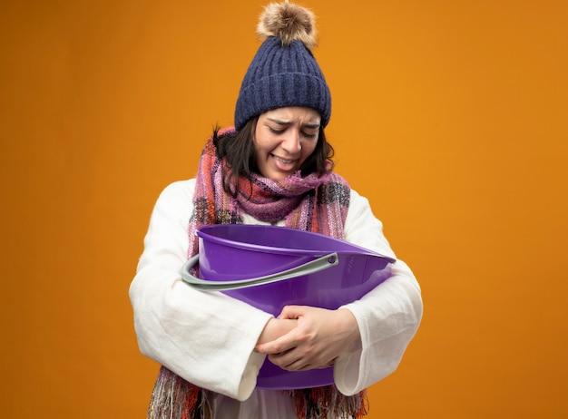 Geïrriteerde jonge blanke ziek meisje draagt gewaad winter hoed en sjaal met plastic emmer met misselijkheid kijken in emmer weergegeven: tong geïsoleerd op oranje muur met kopie ruimte