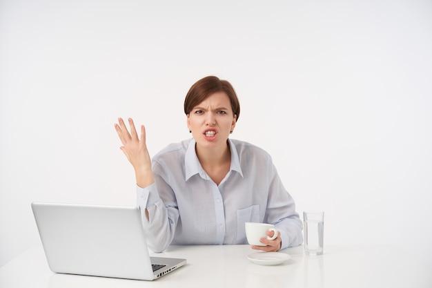 Geïrriteerde jonge bruinharige vrouw met natuurlijke make-up die emotioneel haar hand opheft terwijl ze boos kijkt, een gestreste dag heeft, zittend op wit