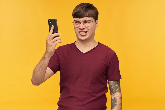 Geïrriteerde jonge man, draagt rood t-shirt en ronde bril, kijkt naar de weergave van zijn telefoon met negatieve gezichtsuitdrukking