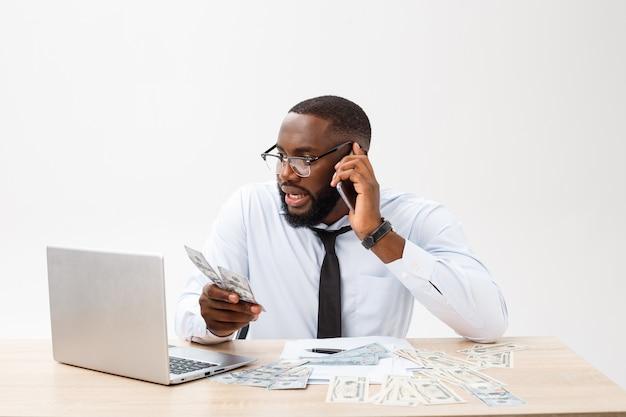 Geïrriteerde jonge mannelijke ondernemer met donkere huid die op de werkplek is voelt zich erg gestrest en boos omdat het niet lukt om alle