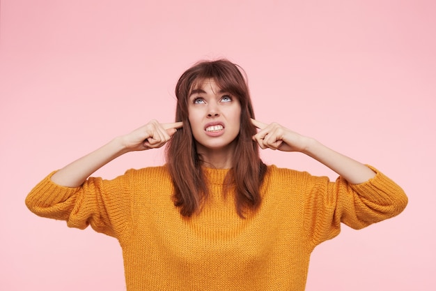 Geïrriteerde jonge mooie brunette vrouw steekt wijsvingers in haar oren terwijl ze harde geluiden probeert te vermijden, fronst haar gezicht terwijl ze naar boven kijkt, geïsoleerd over roze muur