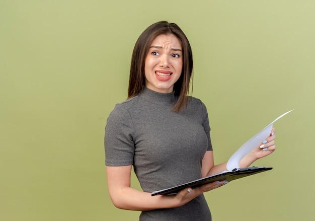 Geïrriteerde jonge mooie vrouw die kant bekijkt en klembord op olijfgroene muur houdt