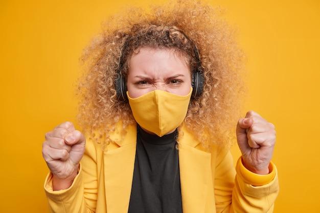 Geïrriteerde jonge vrouw met krullend haar balt haar vuisten van woede uit negatieve emoties omdat ze de quarantaine beu is draagt een beschermend masker luistert naar muziek in stereo draadloze koptelefoon poseert binnen