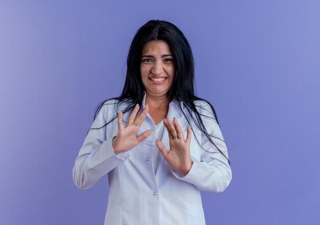 Geïrriteerde jonge vrouwelijke arts die medische mantel draagt die geen gebaar doet