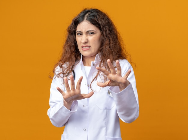Geïrriteerde jonge vrouwelijke arts met een medisch gewaad en een stethoscoop die een weigeringsgebaar doet geïsoleerd op een oranje muur met kopieerruimte
