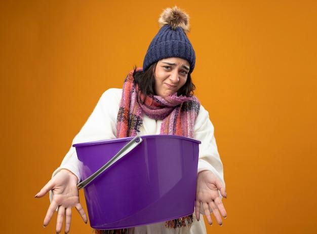 Geïrriteerde jonge zieke vrouw die de muts en de sjaal van de robe-winter draagt ?? die aan voorzijde kijkt die zich uit plastic emmer naar voorzijde uitstrekt die op oranje muur wordt geïsoleerd