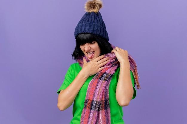 Geïrriteerde jonge zieke vrouw die de winterhoed en sjaal draagt die keel houdt neerkijkt geïsoleerd op purpere muur met exemplaarruimte