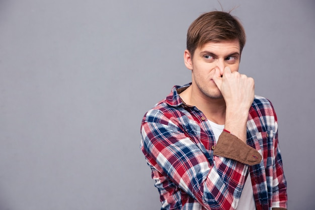 Geïrriteerde knappe jongeman in geruit hemd bedekte zijn neus vanwege slechte geur over grijze muur