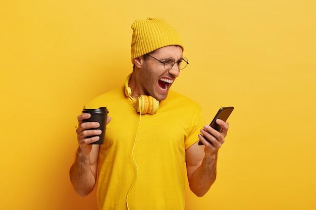Geïrriteerde man kijkt boos naar smartphone, ontvangt een onaangenaam bericht, schreeuwt negatief