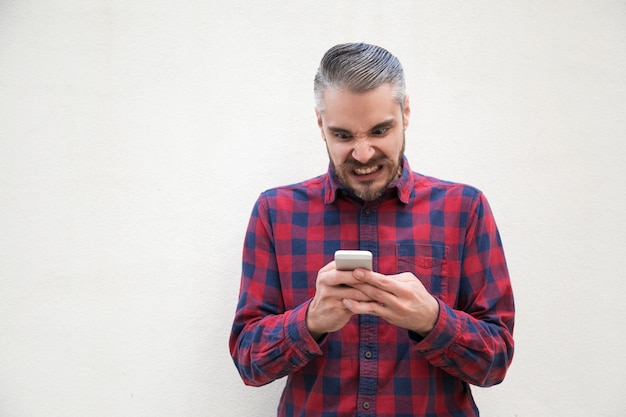 Geïrriteerde man met behulp van de mobiele telefoon