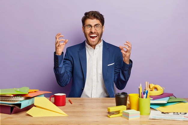 Geïrriteerde mannelijke baas draagt elegant pak, steekt zijn hand op en schreeuwt boos naar collega's, eist om op tijd te werken, zit aan houten tafel met koffie om te gaan