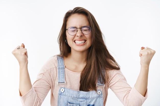 Geïrriteerde, onder druk gezette en beu jonge vrouwelijke collega die tanden op elkaar klemt en ogen sluit