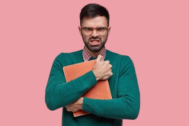 Geïrriteerde ongeschoren mannelijke volwassene heeft een geïrriteerde uitdrukking, houdt boek nauwlettend bij, draagt een bril met dikke lenzen