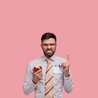 Geïrriteerde ongeschoren ondernemer wijst naar lege ruimte boven, fronst gezicht van ontevredenheid, draagt grote bril, eet rode appel
