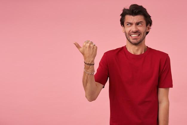 Geïrriteerde ontevreden jongeman met borstelhaar in rode t-shirt die naar de zijkant kijkt en met duimvinger naar lege ruimte wijst