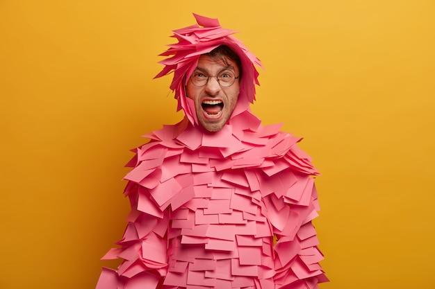 Geïrriteerde, ontevreden man schreeuwt boos, drukt negatieve emoties uit, houdt de mond wijd open, geïrriteerd door iets, draagt een optische bril, papieren kostuum, bedekt met stickers, poseert binnen