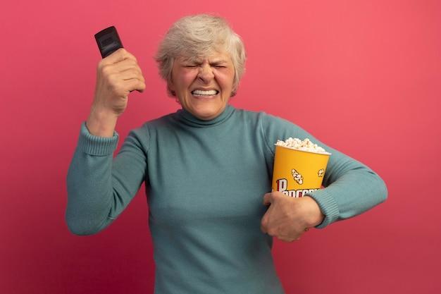 Geïrriteerde oude vrouw met een blauwe coltrui met een emmer popcorn en een afstandsbediening bij het hoofd met gesloten ogen